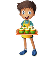 A young man holding a tray with cupcakes vector image vector image