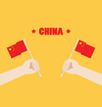 hands holding up china flags vector image