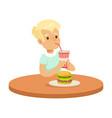 Cute boy drinking a soda through a straw and vector image