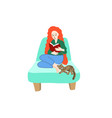 Girl with bright red hair sits in an armchair and
