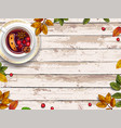 autumn leaves and mulled wine on wooden background vector image
