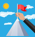 businessman hand puts flag on peak of mountain vector image