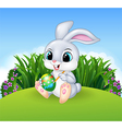 Cartoon Easter Bunny painting an egg in the jungle vector image