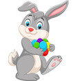 cartoon easter bunny carrying colorful eggs vector image vector image