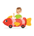 cute little boy riding on toy fish car kid have a vector image vector image