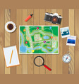 wooden table with paper map planning trip vector image vector image