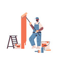 professional worker in uniform using painting wall vector image