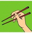 Human hand holding sushi sticks vector image
