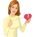Young beautiful girl repairs fabric heart vector image