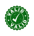 valid scratched stamp with tick vector image vector image