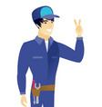 young asian mechanic showing the victory gesture vector image vector image