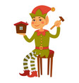 elf sits on stool and builds toy house vector image vector image