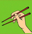 pop art hand with sushi chopsticks vector image