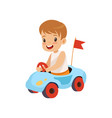 cute smiling boy riding toy car vector image