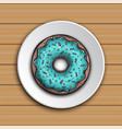 donut with mint glaze on a white plate on the wood vector image vector image