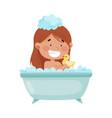 cheerful girl taking a bath sitting in bathtub