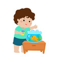 cute little boy feeding fish in aquarium vector image vector image