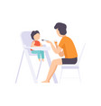 young father feeding baby sitting in the highchair vector image