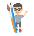 smiling boy holding big pencil and paintbrush vector image
