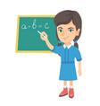 caucasian schoolgirl writing on the blackboard vector image