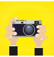 Retro photo camera with hand holding it vector image vector image