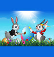 two easter bunnies painting an eggs in a field vector image vector image