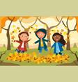 three happy kids plying amongst autumn leaves