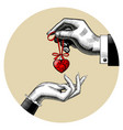 man gives a red toy heart in womans hand vector image vector image