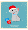 Gray kitten in red hat with two christmas balls vector image