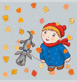 a kid with his dog strolls under the autumn rain vector image