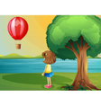 A girl watching the hot air balloon at the vector image