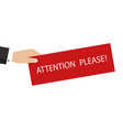 hand holding banner with pay attention please