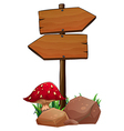 A red mushroom near the wooden arrowboards vector image vector image