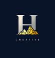 letter h with golden mountain logo de vector image vector image