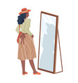 woman in skirt looking in mirror in fitting room vector image vector image