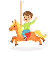 cute little boy riding on the carousel horse kid vector image vector image