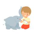 cute little boy feeding baelephant with milk vector image vector image