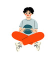 tennage boy sitting cross legged and holding ball vector image vector image