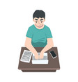 male journalist sitting at desk writing article
