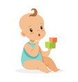 sweet little baby sitting and playing with cubes vector image vector image