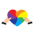 hands holding a rainbow colored heart vector image vector image