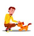 Teen guy volunteer feeding dog in shelter