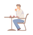 man drinks coffee at a table in a cafe vector image vector image