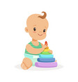 cute smiling baby sitting and playing with pyramid vector image vector image