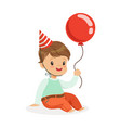 adorable baby boy wearing a red party hat sitting vector image vector image