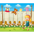 A backyard with hanging clothes and a young girl vector image vector image