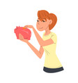 young woman putting coin into piggy money box vector image