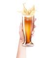 realistic beer glass splashing in hand vector image