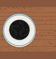 black cumin seeds in a plate on a wooden planks vector image vector image