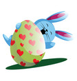 blue bunny holding easter egg with painted hearts vector image